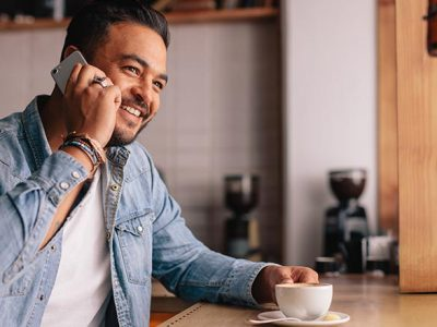 Indoor shot of handsome young man in coffee shop talking on mobile phone. Caucasian guy sitting at cafe making a phone call and looking away.